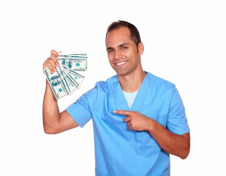 Portrait of a cheerful man in nurse uniform holding cash money on isolated background photo