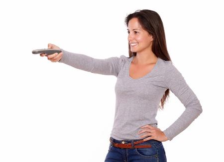 Portrait of a pretty lady pointing remote control