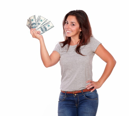 Portrait of a cute smiling lady holding dollars while standing on white background