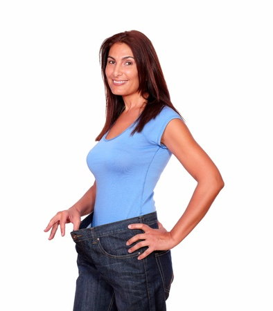 Portrait of a gorgeous senior woman in old jeans pant after losing weight standing over white background