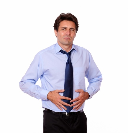 Portrait of a latin adult man with stomach pain against white background photo