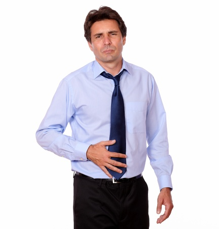 Portrait of a hispanic adult man with stomach pain against white background photo