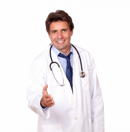 Portrait of a smiling medical doctor extending handshake at you over white background photo