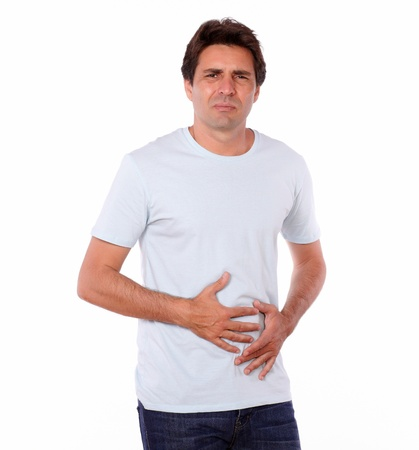 Portrait of an attractive male with pain in stomach while standing on isolated background Stock Photo