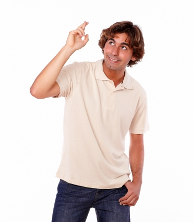 crossing fingers: Portrait of an attractive latin young man crossing fingers while standing on isolated background - copyspace Stock Photo