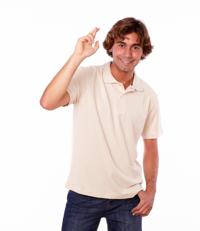 crossing fingers: Portrait of a handsome latin young man crossing fingers on isolated background