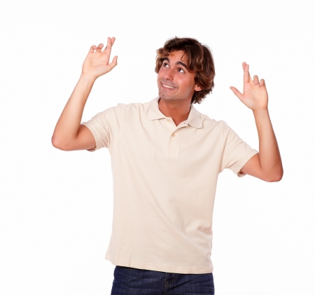 crossing fingers: Portrait of an attractive man crossing fingers while looking up on white background - copyspace