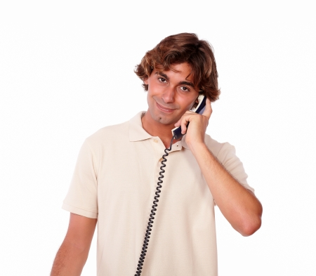 conversing: Portrait of a hispanic handsome man conversing on phone while standing on white background