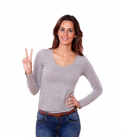 Portrait of a pretty female showing victory sign with fingers on white background
