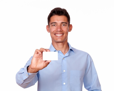 A portrait of an attractive hispanic man holding a blank business card while smiling at you on isolated background - copyspace photo