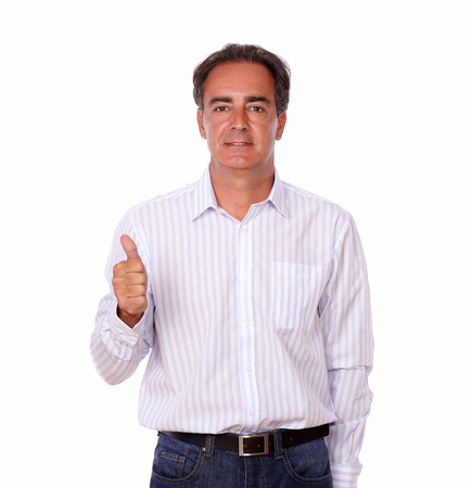 Portrait of a charming hispanic man with ok sign looking at you while standing on isolated studio photo