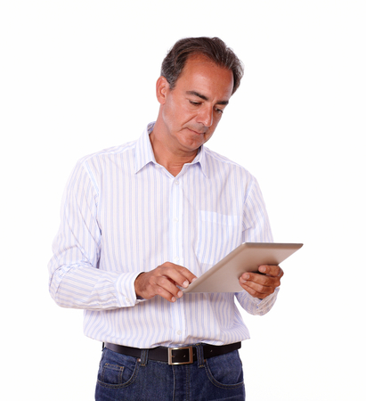 Portrait of a mature hispanic man using his tablet pc while standing