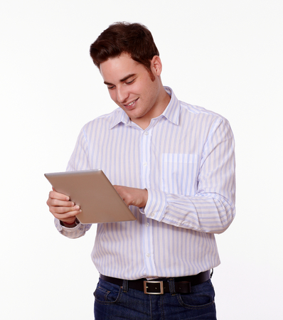 Portrait of a caucasian adult man on white shirt working on his tablet pc on isolated studio photo