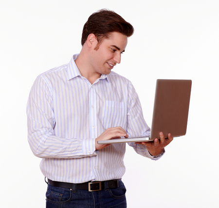 Portrait of a charismatic young man on white shirt standing and smiling while is working on his laptop computer on isolated studio Stock Photo