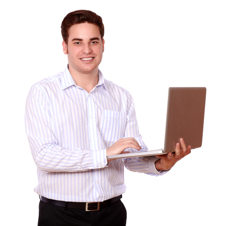 Portrait of an attractive caucasian guy using his laptop while standing and looking at you on isolated studio photo