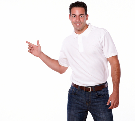 Portrait of an attractive man on white t-shirt pointing to his right while looking at you on isolated background - copyspace photo