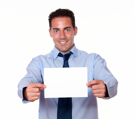 cute guy: Portrait of a cute hispanic guy on blue shirt and tie holding a white blank card while smiling at you on isolated background - copyspace