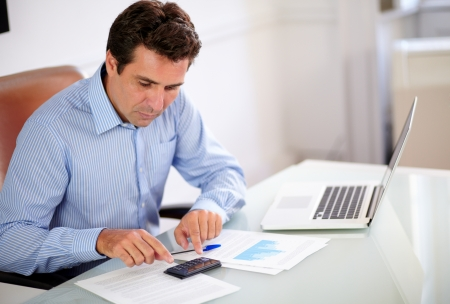 Portrait of a hispanic employee on blue shirt working with his calculator while sitting on office desk photo