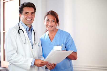 Portrait of a medical colleagues looking and smiling at you while holding documents - copyspace photo