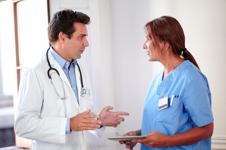 Portrait of a handsome hispanic medical doctor on white coat talking with a nurse woman on blue uniform while standing photo