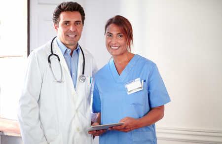 Portrait of a handsome doctor and pretty nurse on medical uniform looking at you while standing and holding a tablet pc photo