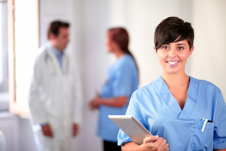Portrait of a lovely latin nurse on blue uniform standing and smiling on medical team background Stock Photo