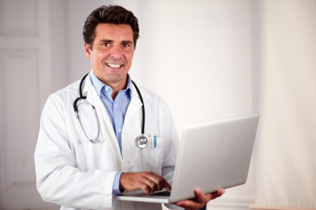 Portrait of a charming adult doctor on white coat and stethoscope using his laptop while standing and smiling at you on hospital photo