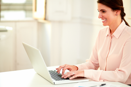 Portrait of a young businesswoman on pink blouse working with her laptop while smiling and sitting on office desk - copyspace photo