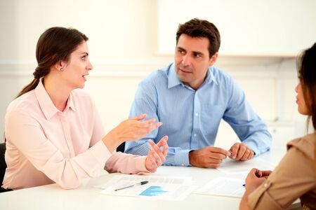 poner atencion: Ejecutivo de sexo femenino que explica una idea a sus colegas mientras escuchan y prestan atenci�n con mucho inter�s