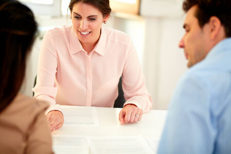 Portrait of adult financial advisor lady explaining an application form to a young couple while listen and sitting on office desk