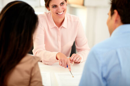 bank manager: Portrait of young caucasian bank manager working on agreement contract and explaining the application form to a businessman at indoors Stock Photo