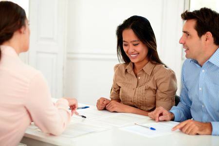 insurance agent: Portrait of young couple working with financial advisor while smiling and sitting on assistance workplace