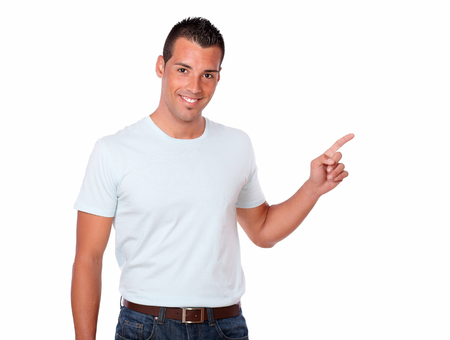 Hispanic man in white t-shirt and jeans pointing to his left