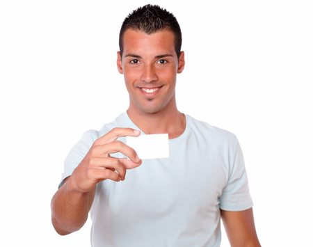 Portrait of a latin man on white t-shirt holding a blank business card while smiling at you on isolated background - copyspace photo