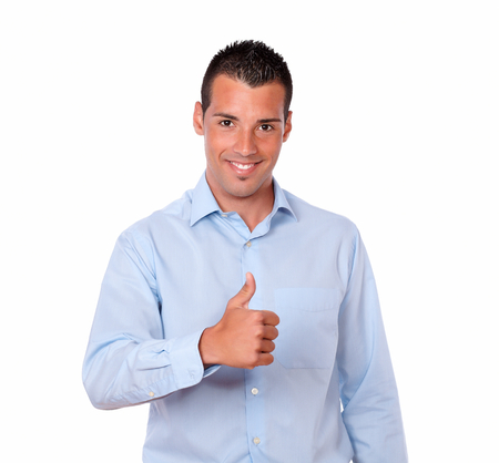 Portrait of a handsome young guy on blue shirt with ok sign standing and smiling at you on isolated studio photo