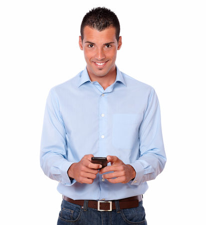 blue shirt: Portrait of a gorgeous young man on blue shirt and jeans texting with his cellphone while standing and looking at you on isolated background