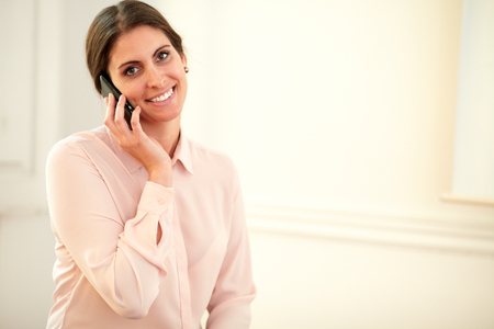 Portrait of young 30s lady on pink blouse talking on her cellphone while smiling at you on closeup background - copyspace photo