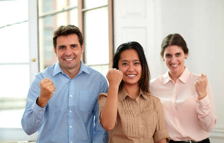 Portrait of professional business team with victory sign smiling at you while standing on office background photo