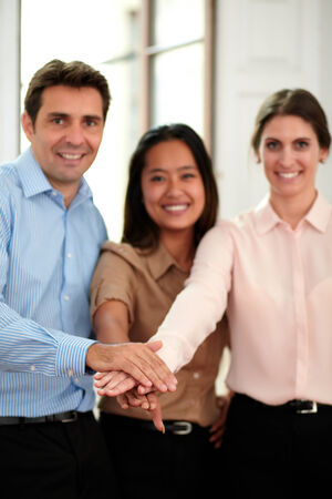 Portrait of group of business people with hands together in unity sign smiling at you and standing on office background photo