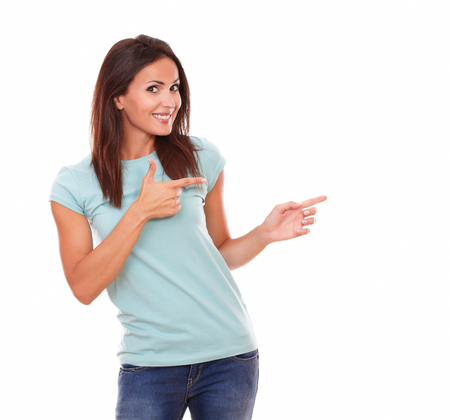 Portrait of fashionable latin lady with funny face on blue t-shirt pointing to her left while standing and smiling at you on isolated white background - copyspace