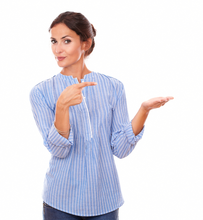 Portrait of single latin lady holding her left palm up while pointing to her left hand and smiling at you on isolated white background - copyspace Foto de archivo