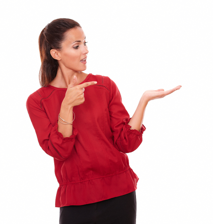 Portrait of young hispanic lady holding her left hand up while pointing and looking to her left on isolated white background - copyspace photo