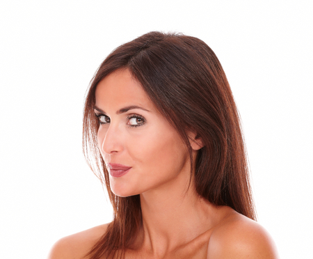 portrait of pretty hispanic female with a smiling like is keeping a secret looking at camera on isolated studio photo