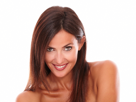 Front view portrait of sexy hispanic woman looking at camera with friendly seductive look and nude shoulders on isolated white background