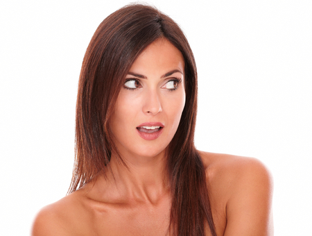portrait of surprised attractive female looking to her left on isolated studio photo