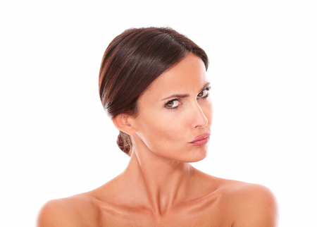 huffy: Human skin portrait of unsmiling hispanic female looking at camera with nude shoulders on isolated white background Stock Photo