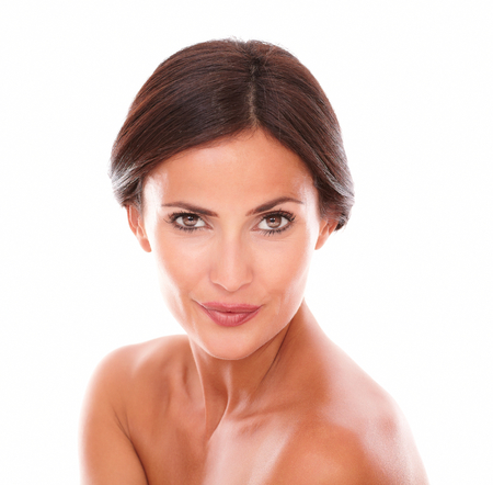 Head and shoulders portrait of charming adult woman looking at camera with nude shoulders and her sensual look on isolated studio Stock Photo