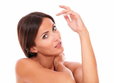 f�minit�: Stylis� t�te et des �paules Portrait de femme hispanique sensuelle pour le produit de soin de la peau montrant sa f�minit� avec les �paules nues tout en regardant la cam�ra sur fond blanc isol�