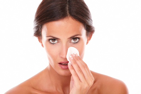 aging woman: Nude shoulders portrait of mature woman pampering her face with cotton and anti aging product while looking at camera on isolated studio