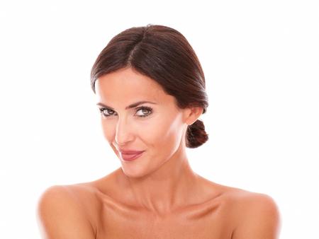 격리 된 스튜디오에 누드 어깨와 미소를 카메라 섹시한 성숙한 여자의 전면보기 초상화